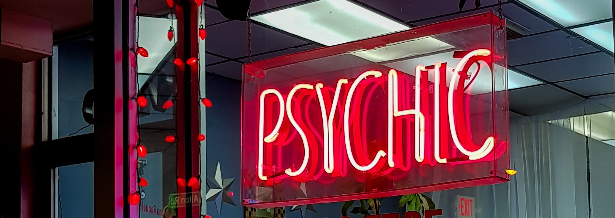 "A red neon window sign with the word ""Psychic"""