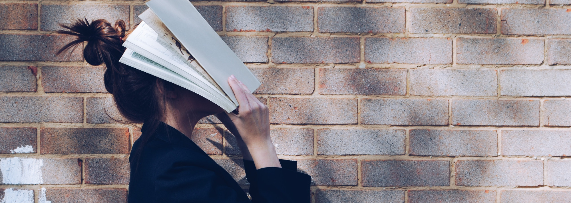 A student with a book covering their face out of frustration