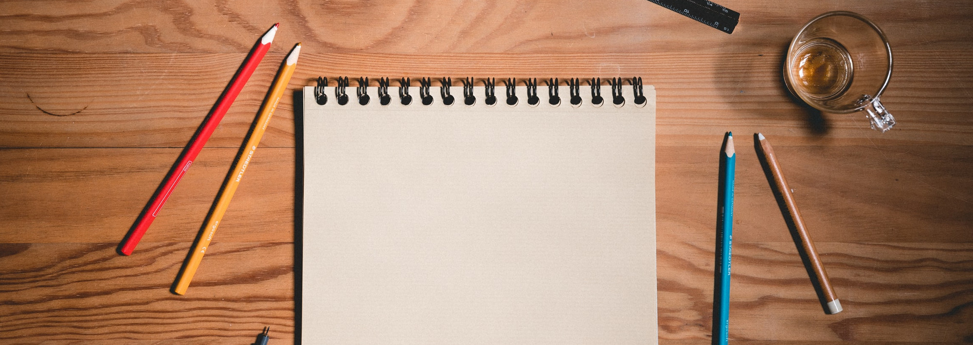 A notebook on a wooden table, with pencils around the notebook. The page is blank.