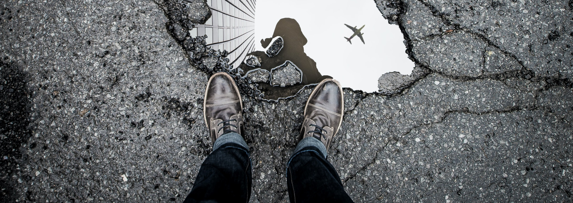 A person standing on a street, looking down at a puddle on the ground. The sky is reflected in the puddle.